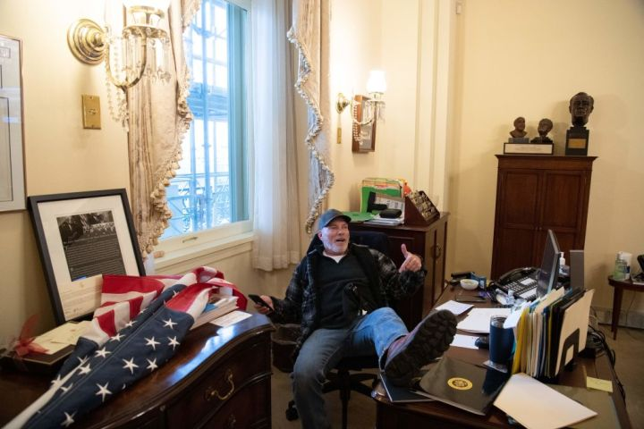 A protester sits in the Senate Chamber after breaking in into the US Capitol Building